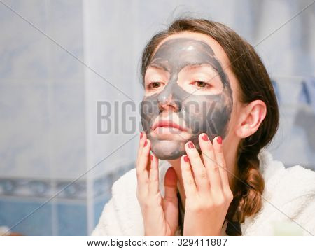 Girl Cares For Oily Skin. Cosmetic Procedures. Skin Care. Young Woman With A Black Mud Mask On Her F