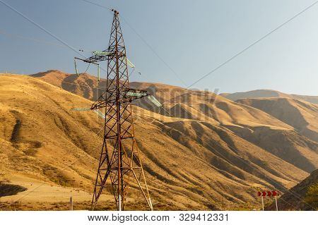 high voltage power transmission pylon in the mountains, high voltage post Mountain landscape poster