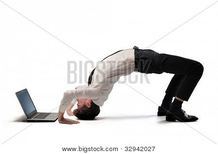 Young businessman doing acrobatics in front of a laptop