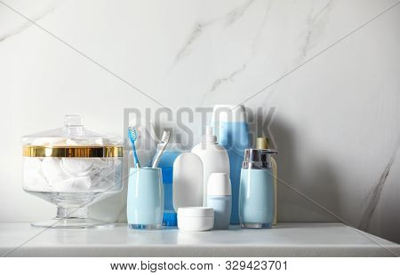 Roll-on deodorant and different toiletry on marble table near light wall poster