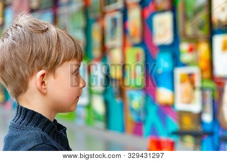 A Surprised Boy Admires Painting At An Exhibition In An Art Gallery.