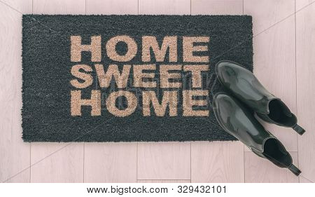 Home Sweet Home doormat entrance mat at front door of new condo in urban city living with stylish womens rain boots of homeowner resting on top.