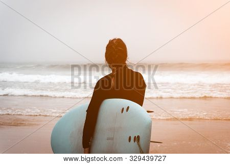 Young Girl Server Stands With A Surfboard By The Ocean. Stormy Weather. Sunny