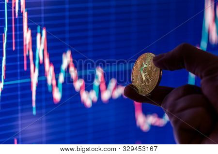 hand holding bitcoin shiner on blurry dark blue exchange chart poster