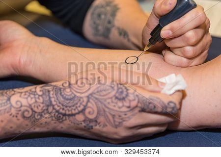 Person Makes Henna Tattoo On His Arm - Mehndi
