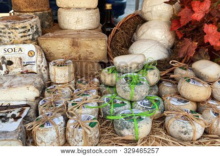 ALBA, ITALY - OCTOBER 04, 2015: Small hard artisan cheese wrapped in straw at the farmers market in old town during famous annual White Truffle festival taking place in Alba, Piedmont, Northern Italy.