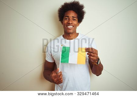 Young african american man holding Ireland Irish flag standing over isolated white background with a happy face standing and smiling with a confident smile showing teeth