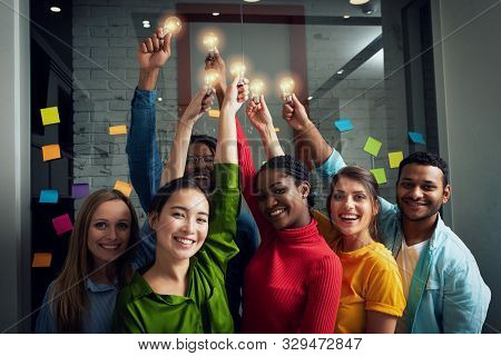 Teamwork And Brainstorming Concept With Businessmen That Share An Idea With A Lamp. Concept Of Start