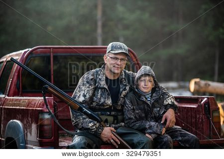 Father And Son Sitting In A Pickup Truck After Hunting In Forest. Dad Showing Boy Mechanism Of A Sho