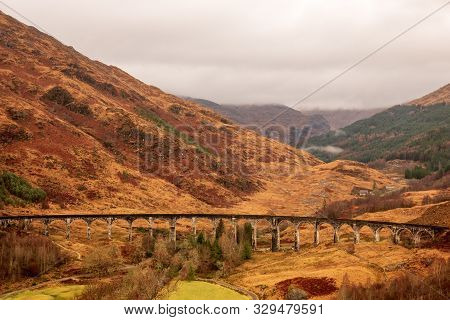 Glenfinnan Viaduct In-between Wintery Brown Fields And Hills On A Cloudy Day In The Scottish Highlan
