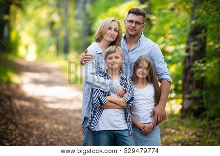 Portrait Of Happy Family Of Four In A Green Summer Park