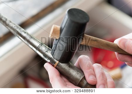 poster of Hardworking Goldsmith Working On An Unfinished 22 Carat Gold Ring With His Hands And Tools