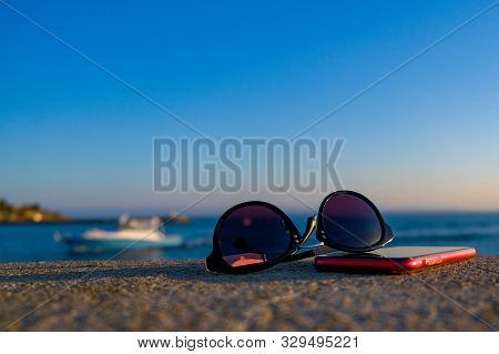 Glasses And Smart Phone On The Concrete Parapet Of The Embankment Of The Mediterranean Sea On Blue S