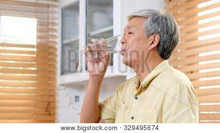 Senior Asian Man Drinking Water While Standing By Window In Kitchen Background, Elderly Retirement P