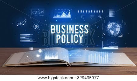 BUSINESS POLICY inscription coming out from an open book, creative business concept