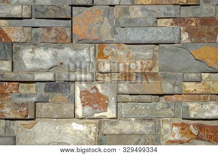 Wild Yellow Decorative Stone Background. Artificial Ocher Decorative Bricks Wall. Construction Made