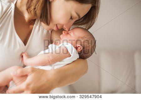 Cute Newborn Baby Sleeping In Mothers Arms. Motherhood.