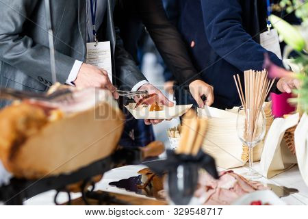Businesspeople At Banquet Lunch Break At Business Conference Meeting. Assortment Of Food And Drinks.