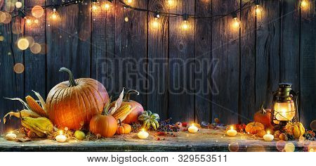 Thanksgiving - Pumpkins On Rustic Table With Candles And String Lights
