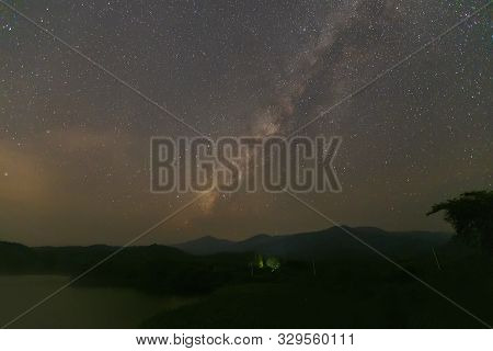 Landscape Of The Milky Way Galaxy With Starlight Over The Mountain With Tree And River On Forground