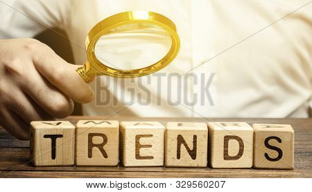 Wooden Blocks With The Word Trends And Businessman With A Magnifying Glass. Popular And Relevant Top