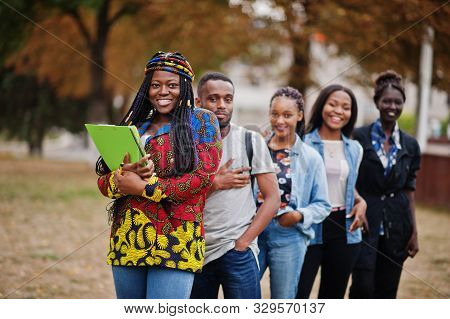 Row Of Group Five African College Students Spending Time Together On Campus At University Yard. Blac