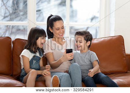 Happy young mommy sitting with children siblings, using mobile phone. poster