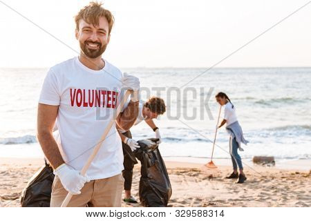 Image of enthusiastic young volunteers cleaning beach from plastic with trash bags at seashore