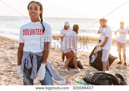 Smiling young african girl volunteer cleaning beach from garbage with group of people volunteers