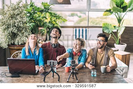 Young millenial friends sharing creative content online - Digital marketing concept with next generation influencer having fun on air with radio video stream - Vlogging time at startup coworking space poster