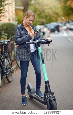 Young Woman With Electric Kick Scooter In The Street Of The City, Looking At Her Phone And Smiling.