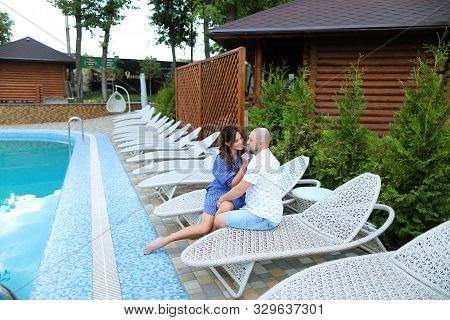 Happy Couple Sitting On White Chaise Longue Near Swiming Pool And Wooden House.