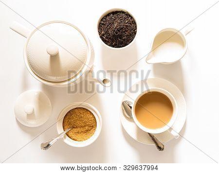 Traditional English Breakfast Black Tea With Milk -tea Leaves. Teacup, Teapot, Sugar And Milk Bowls