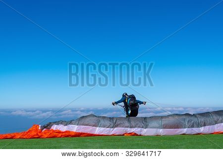Paraglider Preparing Full Flight Equipment And Paragliding Soaring In The Beautiful Blue Sky And Bri