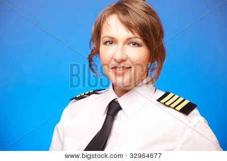 Beautiful woman pilot wearing uniform with epauletes, looking ahead, standing on blue background. poster