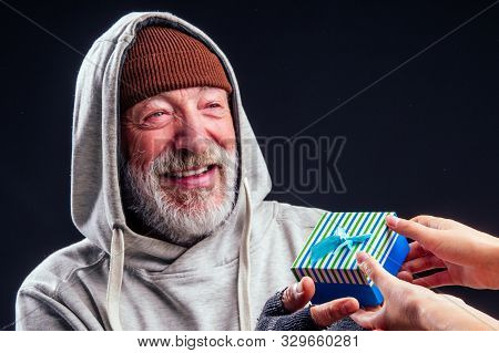 Smilley Portrait Of Old Senior Male Tramp Wearing Warm Brown Hat And Leaky Gloves, Holding Blue Gift