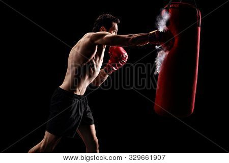 Strong muscular man punching a bag with boxing gloves on a black background