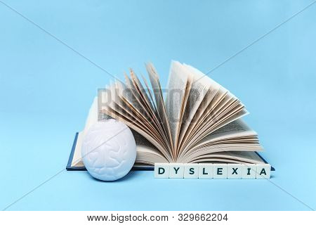 Dyslexia Word With A Brain Stress Relief And Open Book On Blue Background, Reading Difficulty And Di
