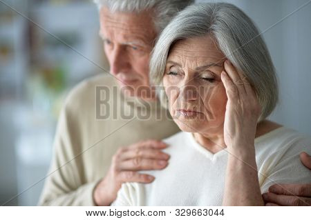 Close Up Portrait Of Sad Senior Couple Posing