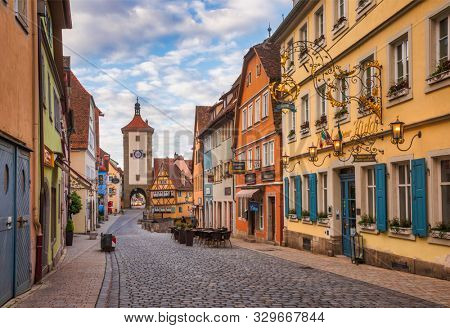 Rothenburg ob der Tauber, Germany - May 10, 2019: Hotels and shops along the Schmiedgasse street with Plonlein (Little Square) and Siebers Tower seen in background