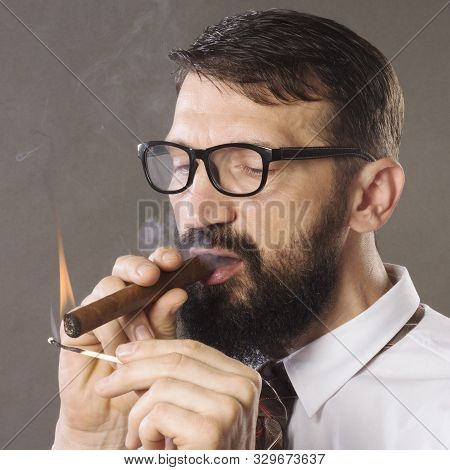 The Elegant Handsome Man In Glasses Is Igniting His Cigar With Matches.