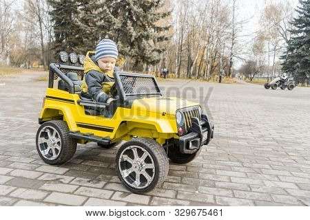Toddler With Enthusiasm Study Control Of Yellow Children Car With An Electric Motor In Autumn City P