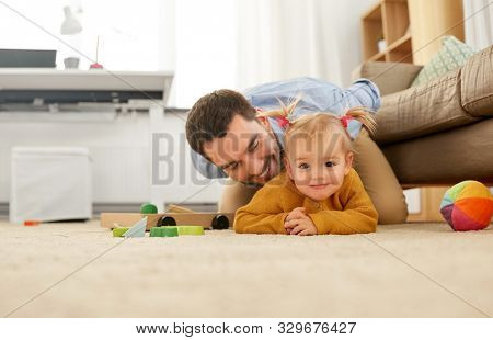 family, parenthood and fatherhood concept - happy father with little baby daughter playing on floor at home