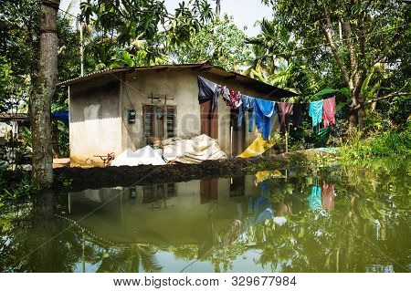 House With Laundy In The Kerala Backwaters In The Lush Jungle Along The Canal With Bright Reflection