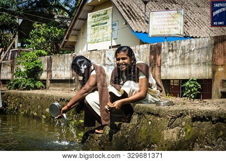Alleppey - Alappuzha, India - 13 November 2017: Student Girls Washing Out Their Bowls Along River In