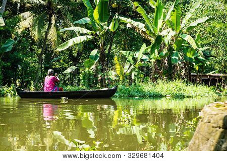 Alleppey - Alappuzha, India - 13 November 2017: Old Local Woman Paddling In A Small Boat Through The