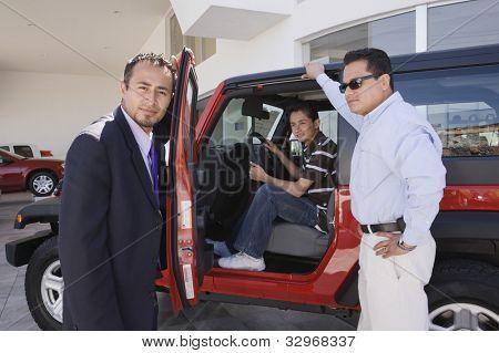 Hispanic father and son at car dealership