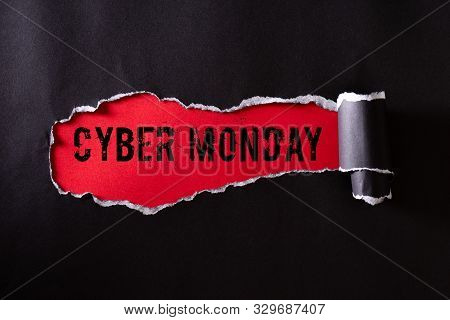 Top View Of Black Torn Paper And The Text Cyber Monday On A Red Background. Cyber Monday Composition