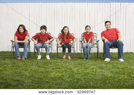 Mixed Race family sitting in lawn chairs