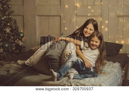 Little Friendly Sisters Fight Pillows. Morning Light Christmas Holiday. Children Play And Have Fun T